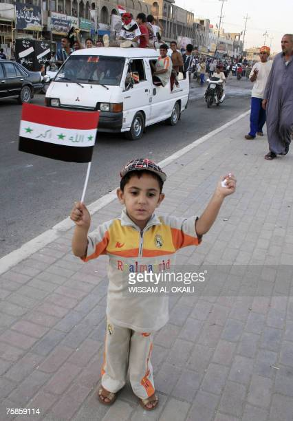 A young Iraqi boy holds his national flag as supporters celebrate the victory of their country's football team against Saudi Arabia for the final of...