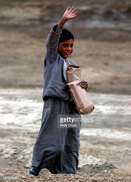 IRAQA young Iraqi boy holds onto several MRE's that were tossed out of a Marine vehicle that was following a massive combat train convoy Monday...