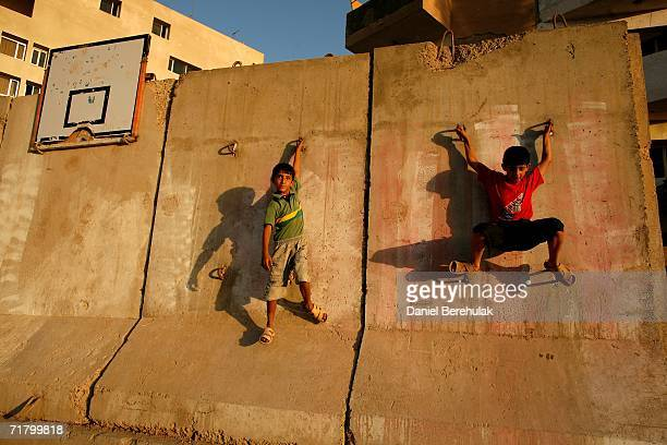 Young Iraqi boys play on a blast wall on September 6 2006 in Baghdad Iraq It was here on October 14 2005 two suicide bombers drove their vehicles...