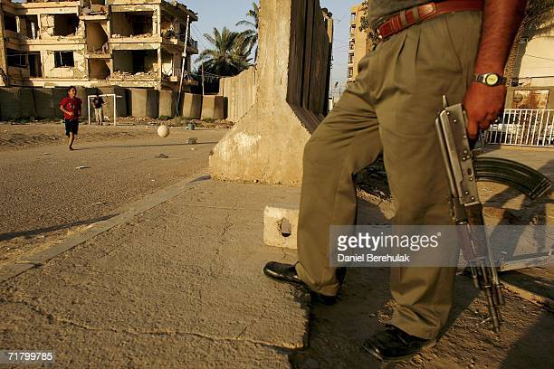 Young Iraqi boys play soccer as a security guard stands watch amongst protective blast walls on September 6 2006 in Baghdad Iraq It was here on...