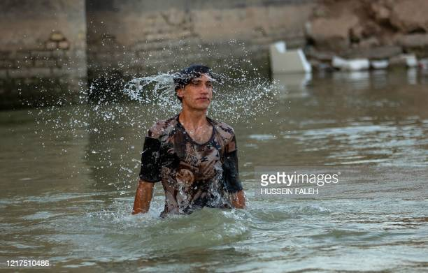 Young Iraqi cools himslef in the Shatt Al-Arab river in the southern city of Basra as temperatures soar in the region, on June 4, 2020.