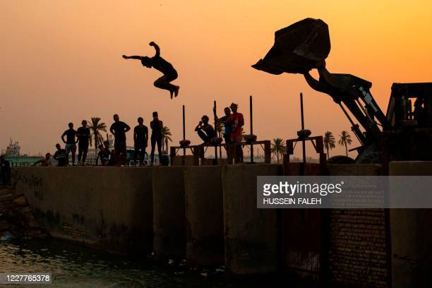 Young Iraqi dives from a bulldozer into the Shatt Al-Arab river at sunset, in the southern port city of Basra, on July 24, 2020.