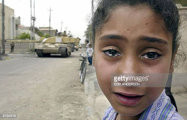 A young Iraqi girl cries as a British Challenger tank moves in on the Baath party office in Basra 08 April 2003 British and coalition forces took...