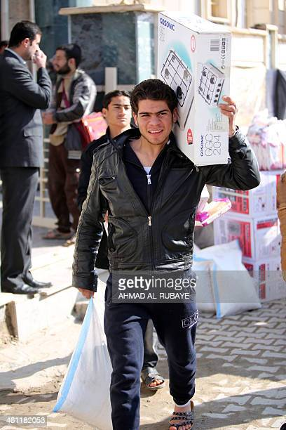 A young Iraqi man who fled Fallujah with his family carries portable stove distributed by the International Organization for Migration NGO on January...