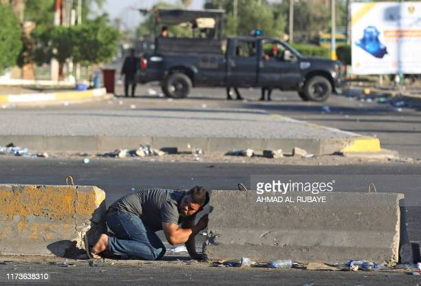 A young Iraqi takes cover between two concrete blocks during a demonstration against state corruption failing public services and unemployment in the...