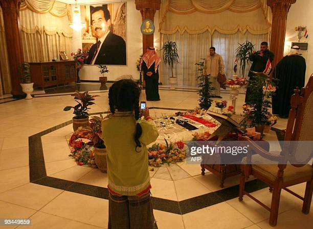 A young Iraqi uses a mobile phone to take a photograph at the grave of former Iraqi president Saddam Hussein at a mausoleum in his home town of Awja...