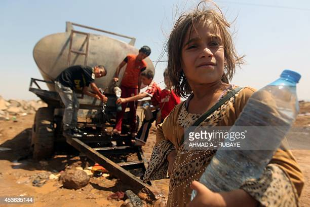 Young Iraqi Yazidi refugees fill bottles with water at the Newroz camp in Hasaka province north eastern Syria on August 14 after fleeing advances by...