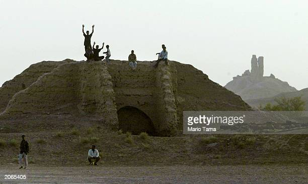 Young Iraqis stand atop ancient ruins in the shadow of a Mesopotamian ziggurat June 8 2003 in Borsippa Iraq The ziggurat a temple tower was built by...