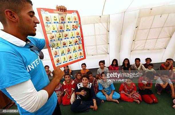 Young Iraqi's that fled violence in the northern city of Tal Afar due to attacks by Islamic State jihadists look up at a teacher during a class at a...