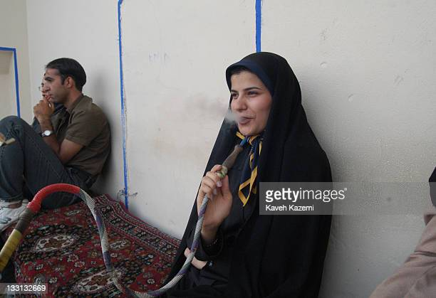 Young Isfahani woman in black chador smokes a water pipe while sitting alone in a teahouse facing Naghsh-e Jahan Square in Isfahan, Iran, July 10th,...