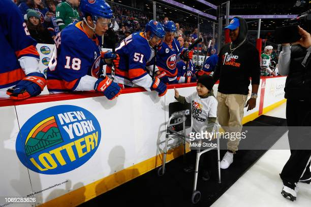 A young Islanders fan highfives Valtteri Filppula of the New York Islanders as part of Hockey Fights Cancer prior to the game against the Dallas...