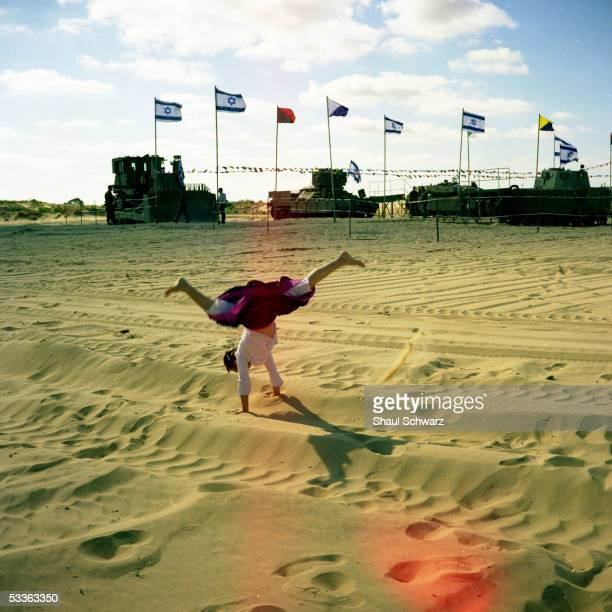 A young Israeli girl plays in the sand dunes as the army prepares a presentation of its tools for the Israeli independence day May 10 2005 in the...