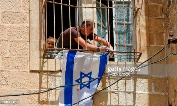 A young Israeli settler fixes the Israeli flag outside the window of a Palestinian house after it was occupied by settlers the previous night near...