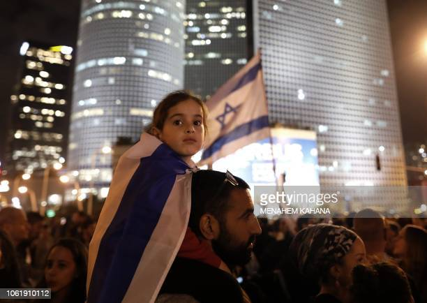 A young Israeli wears a national flag as fellow Israelis protest against a recent cease fire with the Hamas movement in the coastal city of Tel Aviv...