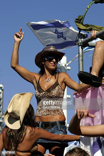 Young Israelis dance at the annual Love Parade at the beach front of Tel Aviv, 21 October 2005. AFP PHOTO/GALI TIBBON