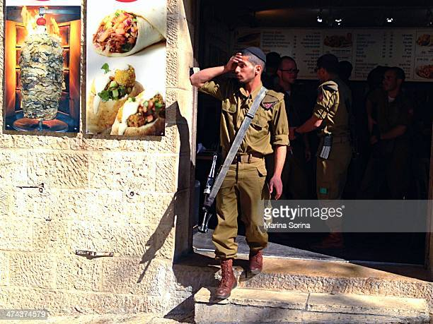 Young Israely soldier relaxing after a lunch break in a fast-food of Old town in Jerusalem, Israel.