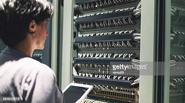 Jovem é Engenheiro de pé perto de datacenter servidores