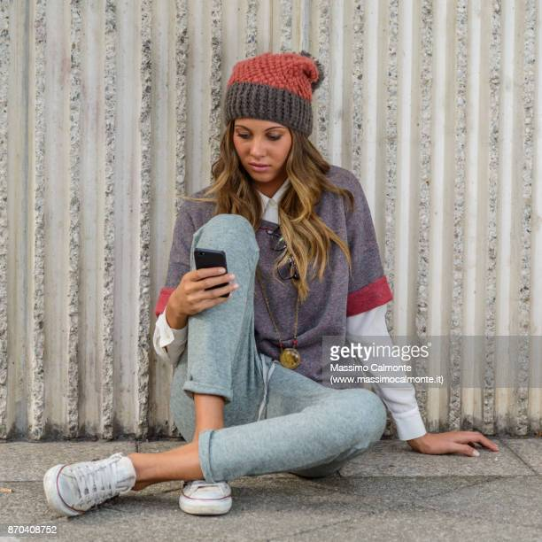 young italian blond girl wearing cap with fashion style and writing on her smartphone mobile - western europe stock pictures, royalty-free photos & images