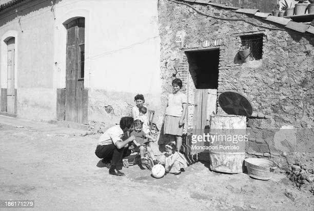 Young Italian southern emigrant Giuseppe Arena playing with his children in front of a poor house He came back to Catania from Turin because of the...