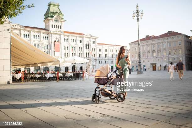 赤ちゃんと一緒に歩く若いイタリア人女性 - トリエステ ストックフォトと画像