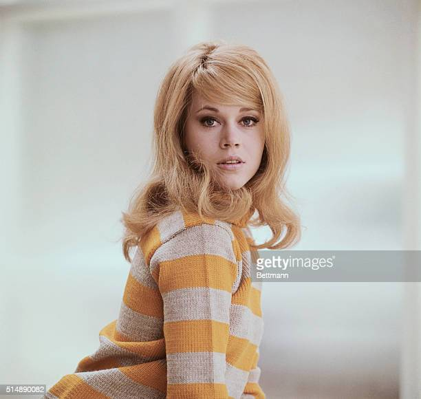 A young Jane Fonda in a waist length shot poses in a mustard yellow sweater