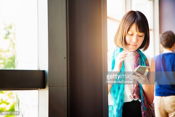 Young Japanes female using mobile phone during business break
