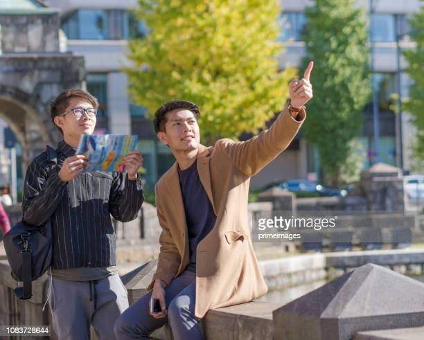 Young japanese and asian friend looking for travel location  using mobile phone and spending time together in japan