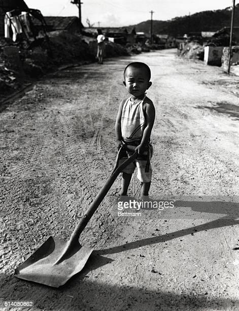 A young Japanese boy stands with a shovel on a street in Hiroshima one year after the United States dropped an atomic bomb on the city