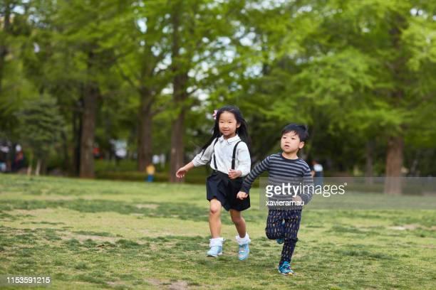 公立公園で走っている若い日本の兄弟姉妹 - 近く ストックフォトと画像