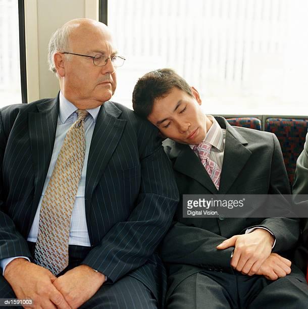 Young Japanese Businessman Asleep on a Mature Businessmans Shoulder