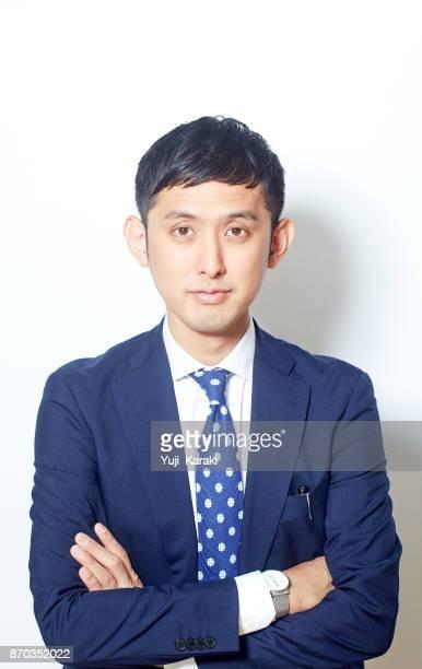 Jeune homme d'affaires japonais dans un costume en regardant la caméra