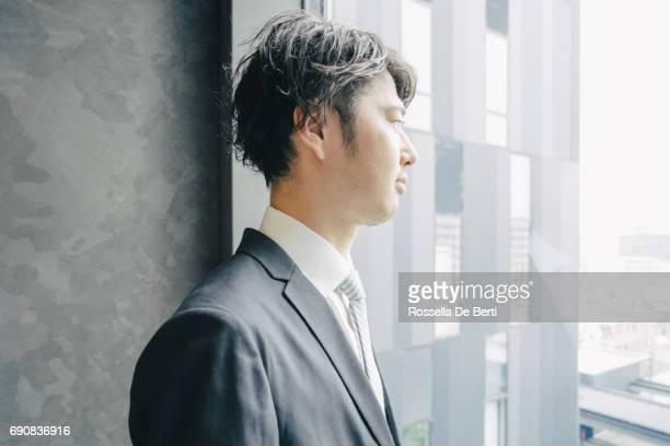 Ung japansk affärsman tittar ut office fönstret