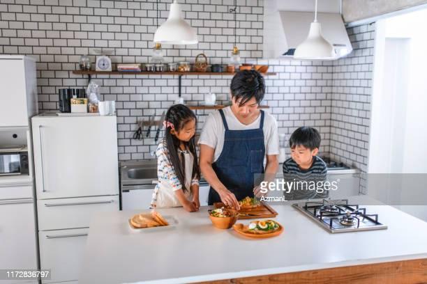 父が昼食を作っているのを観察する日本の若い子供たち - preparing food ストックフォトと画像