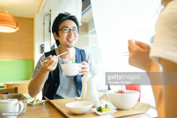 ランチを持っている若い日本人カップル - man eating woman out ストックフォトと画像