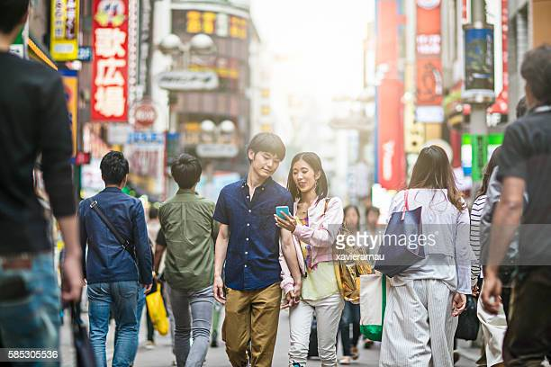 Young Japanese couple playing around the streets of Tokyo