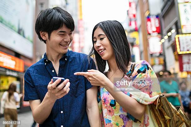 young japanese couple playing around with the mobile phone - homem pegando mulher imagens e fotografias de stock