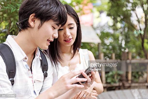 若い日本人夫婦携帯電話を使用