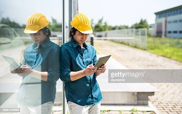 young japanese engineer using digital tablet outdoors. - real estate developer stock pictures, royalty-free photos & images