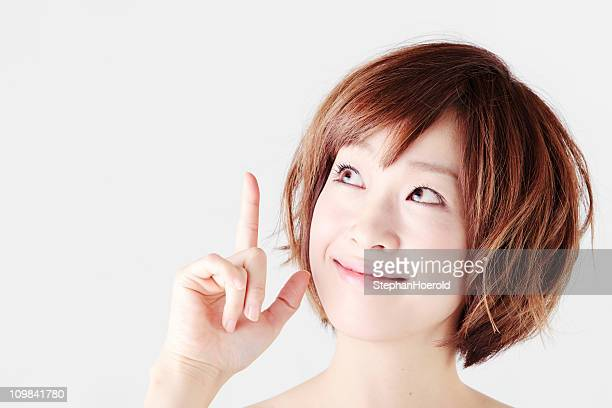 Young Japanese female adult with an inspiration raises finger