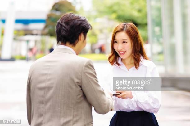 若い日本女性労働者は、お辞儀の同僚に彼女のカードを手します。