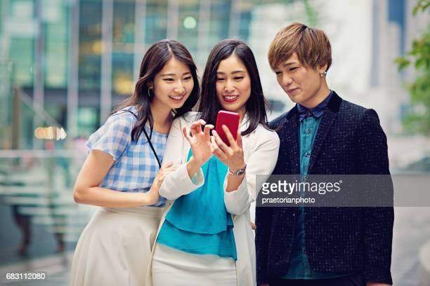 Young japanese friends are looking in a mobile phone