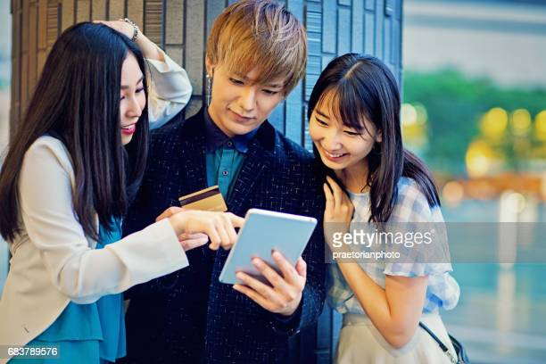 Young japanese friends are shopping online