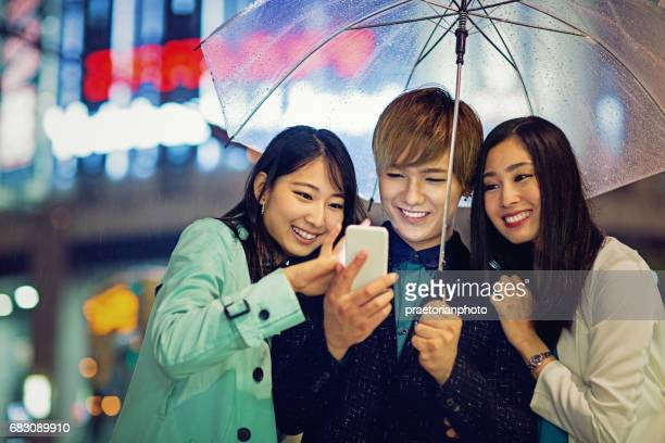 Young japanese friends are texting with a mobile phone in the rainy night