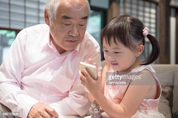 Young Japanese girl and grandfather playing with handheld device