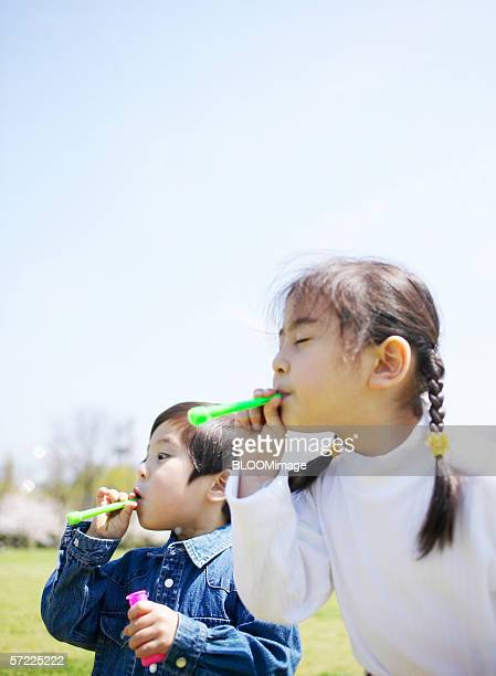 Young Japanese girl & boy playing soap bubbles