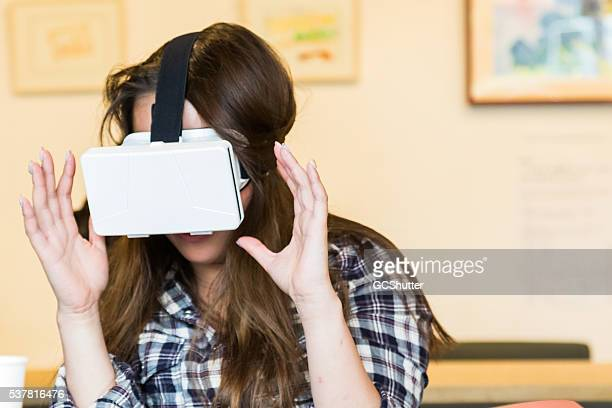 young japanese girl enjoying virtual reality console - head mounted display stock photos and pictures