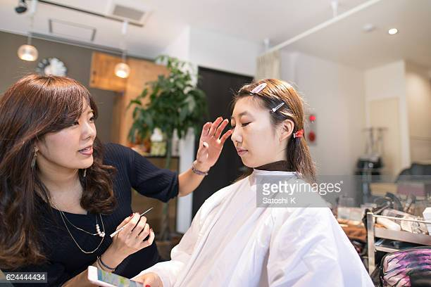 young japanese girl making up in beauty salon - seijin no hi stock pictures, royalty-free photos & images