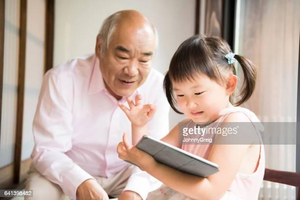 祖父とデジタル タブレットで遊ぶ若い日本人の女の子