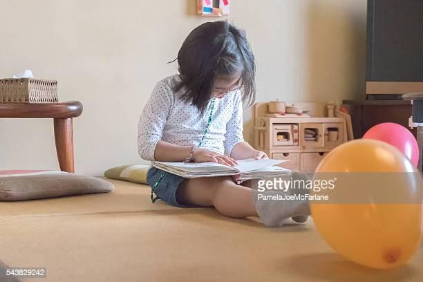 Jovem menina japonesa lê um livro na sala de estar no chão
