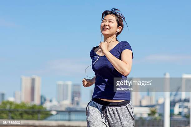 young japanese girl running in the morning at tokyo - 走る ストックフォトと画像